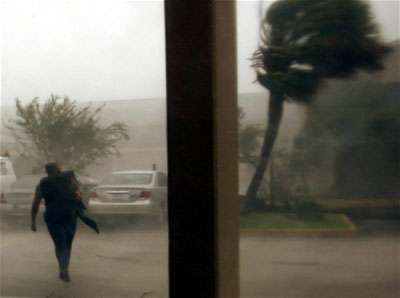 A man walks to his car as fights the winds of Hurricane Katrina