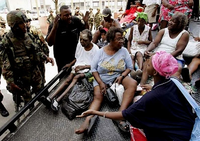 Hurricane Katrina survivors are transported on a flatbed truck