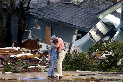 A father comforts his son as they view their destroyed home