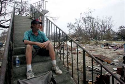 Stairs to Nowhere: A reflective Hurricane Katrina survivor sits on a staircase next to a destroyed building