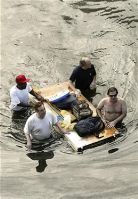 Four Hurricane Katrina survivors transport some personal items on a makeshift float
