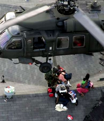 A National Guard Member prepares Hurricane Katrina survivors for an air rescue